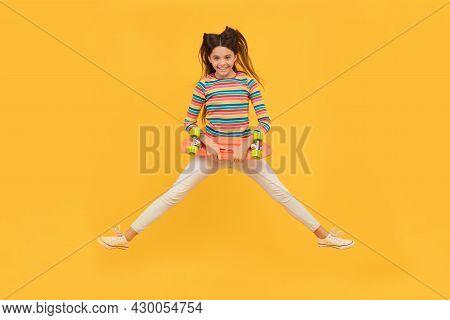 Happy Energetic Kid Skateboarder Jumping With Penny Board Skateboard, Childhood
