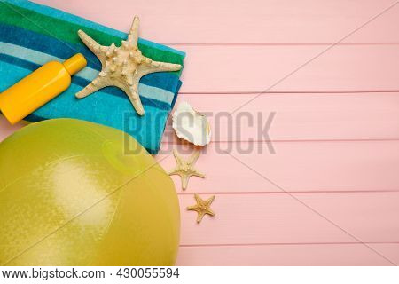 Beach Ball, Blanket, Sunscreen And Starfishes On Pink Wooden Background, Flat Lay. Space For Text