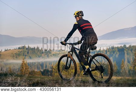 Male Cyclist In Cycling Suit Riding Bike With Coniferous Trees And Hills On Background. Man Bicyclis