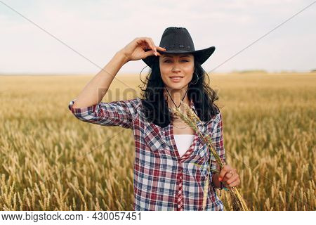Woman American Farmer Smiling With Sheaf Wheat Ears Wearing Cowboy Hat, Plaid Shirt And Jeans At Whe