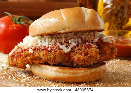Chicken parmesan sandwich (seasoned and fried chicken breast with tomato basil marinara sauce and mozzarella on a grilled bun) with ingredients and cooking oil in background.  Macro with shallow dof.