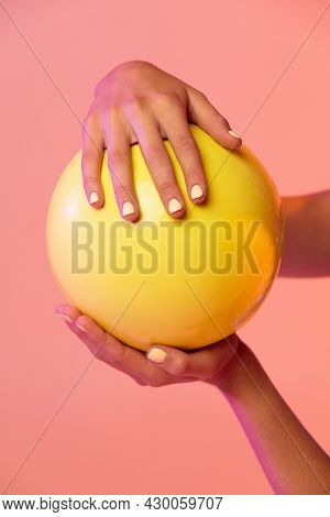 Close-up Female Hands And Rhythmic Gymnastics Yellow Ball Isolated On Gradient Pink Yellow Studio Ba
