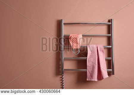 Modern Heated Towel Rail With Cloth Face Mask And Towel On Light Pink Wall. Space For Text
