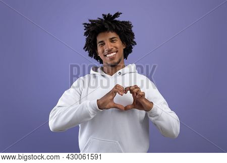 Kind Black Teenager Shaping Hands Like Heart Near His Chest, Making Love Gesture On Violet Studio Ba
