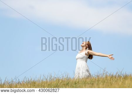 Excited Woman Screaming To The Air Outstretching Arms In A Wheat Field