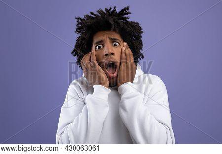 Black Teen Guy Feeling Scared, Shouting In Panic On Violet Studio Background