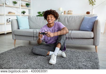 Full Length Of Positive Black Teen Gamer With Controller Playing Online Video Games, Sitting On Floo