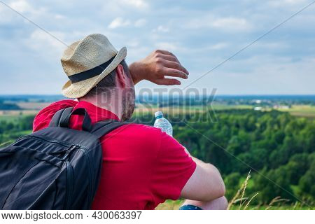 Man With Backpack Hiking Wipe The Sweat And Hold The Water Bottle On The Mountain Forest. Backpack S