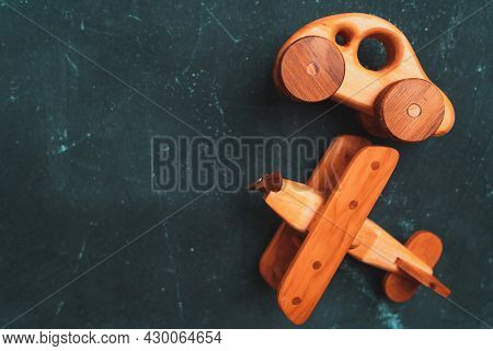 Wooden Toy Car And Biplane On A Dark Background, Top View