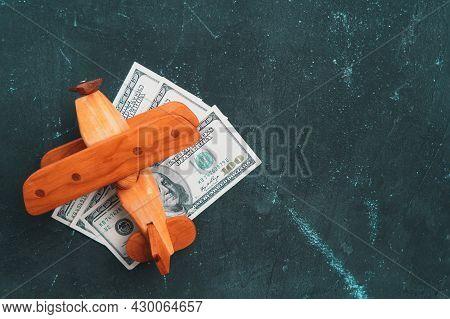 Wooden Toy Airplane Biplane Stands On Paper Dollar Bills, Dark Background Copyspace