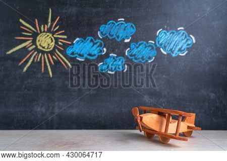 Wooden Toy Airplane Biplane On The Background Of A Chalk Board With A Pattern Of Clouds And The Sun