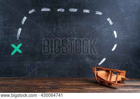 Wooden Toy Airplane Biplane On The Background Of A Chalk Board With A Drawing Meaning The Route And