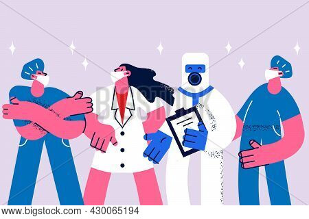 Doctors In Masks During Covid-19 Epidemic Concept. Group Of Young Doctors Men And Women Wearing Prot