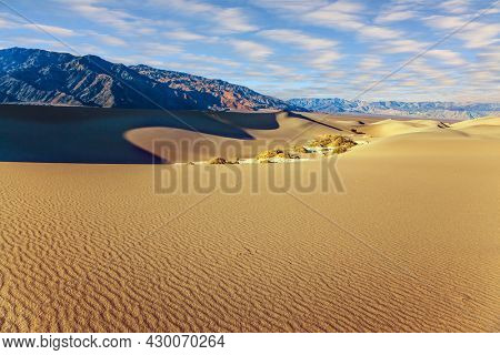 The gentle slopes of the sand dunes are rippled by the wind. USA. Concept of active, ecological and photo tourism. Mesquite Flat Sand Dunes is a picturesque part of Death Valley in California