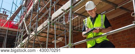 Panorama male builder foreman, construction worker, contractor or architect on building site writing on black clipboard panoramic web banner header
