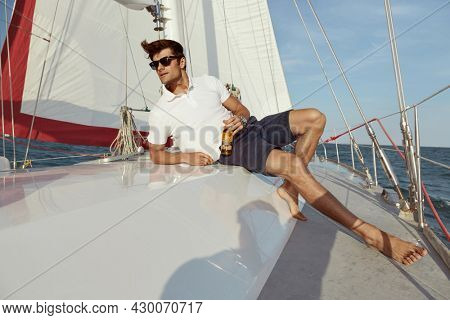 Focused young man lying and drinking beer on his yacht in sea or ocean. Luxury boat. Guy wear shorts, shirt and glasses. Concept of sailing vacation or tourism. Summertime. Sunny daytime