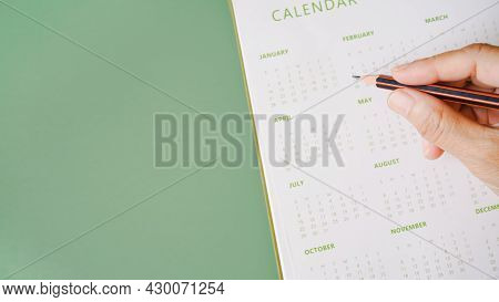 Hand Holding Pencil With Blurred Yearly Calendar For Planning Work ,monthly Or Yearly Schedule , Mak