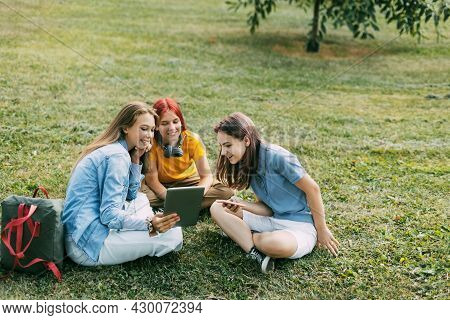 Teenage Girls Sit On The Green Lawn In The Park During A Break. Education And Knowledge, Lifestyle O