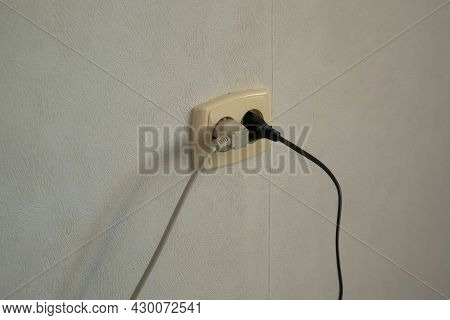 Mans Hand Turns The Plugs Of An Electrical Appliances Into An Outlet. Man Is Turning On The Forks On