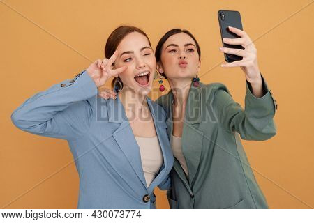 Young two women gesturing while taking selfie on cellphone isolated over yellow background