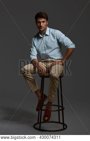 Young beautiful confident european businessman sitting on bar chair. Bearded man with dark hair wear shirt with trousers and looking at camera. Isolated on dark gray background. Studio shoot