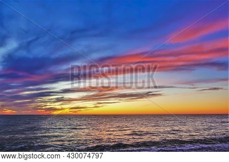 Colorful Sunset Over The Sea. The Sky Is Orange. The Clouds Are Highlighted In Scarlet. The Sea Is C