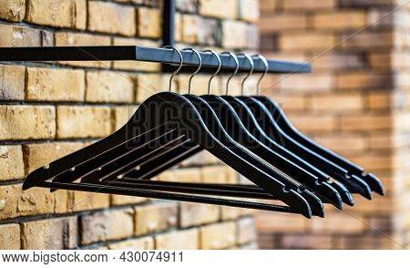Fashionable Different Types Of Hanger. Wood Hangers Coat. Many Wooden Black Hangers On A Rod. Store
