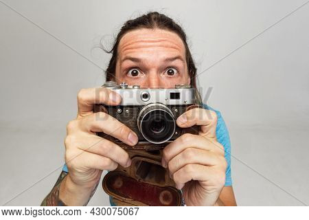 High Angle View Of Young Man, Photographer, Cameraman With Retro Camera Isolated On Gray Studio Back