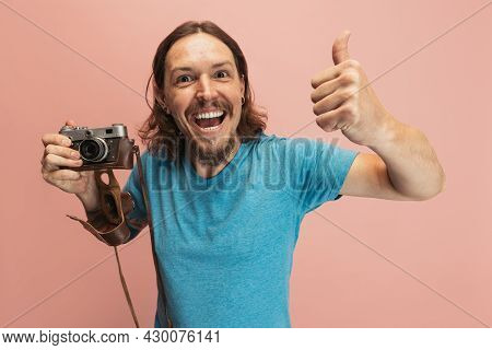 Portrait Of Young Man, Photographer, Cameraman With Retro Camera Isolated On Pink Studio Background.