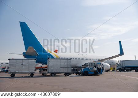 Airfield Tractors Near Big Modern Airplane Ready For Boarding In Airport Hub On A Daytime