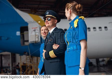 Confident Pilot In Uniform And Aviator Sunglasses Walking Together With Two Air Stewardesses In Blue