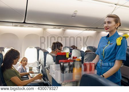 Female Flight Attendant Serving Food To Passengers On Aircraft. Hostess Walking With Trolley On Aisl