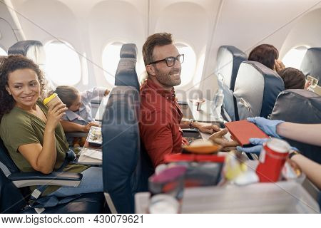 Happy Passengers Smiling While Female Flight Attendant Serving Lunch On Board