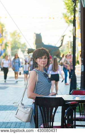 A Brunette Woman Stands Near A Table Of A Street Cafe In A European City On A Busy Street.