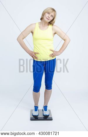 Mature Caucasian Sportswoman In Jogging Blue And Yellow Outfit Checking Weight With Floorstanding We
