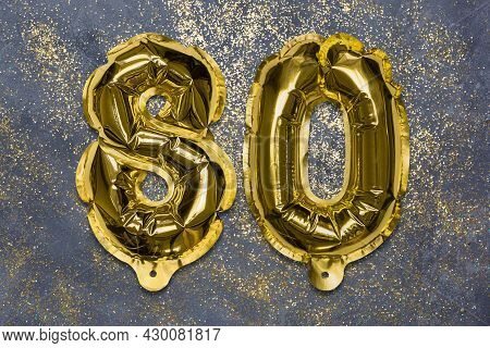 The Number Of The Balloon Made Of Golden Foil, The Number Eighty On A Gray Background With Sequins.
