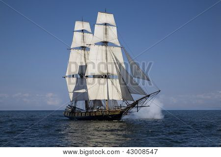 Tall Ship With Cannons Firing Sailing On Blue Waters