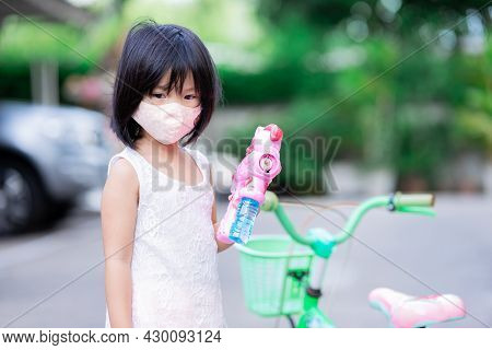 Cute Girl Wearing An Orange Cloth Face Mask Is Feeling Sad Because The Bubble Gun Can't Play Because