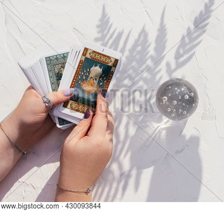 Hands With Purple Nails And Rings Hold Deck Of Tarot Cards On White Surface With Crystal Ball And Fe