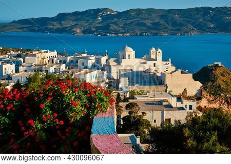 Picturesque scenic view of Greek town Plaka on Milos island over red geranium flowers and Orthodox greek church. Plaka village, Milos island, Greece