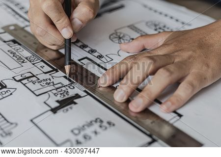 Architect Uses A Ruler To Measure The Blueprints Of The Houses He Designed, Designing The Buildings