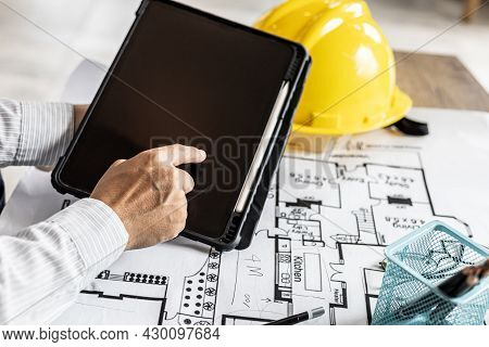 Architects Are Looking At Blueprints Designed On Tablets, Designing The House According To The Homeo