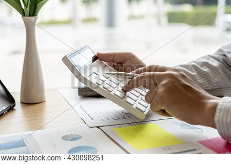 The Financial Officer Presses The White Calculator, He Calculates The Numerical Balance On The Docum