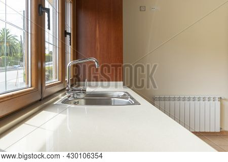 Metal Faucet In Modern Kitchen With White Granite Top Illuminated By Large Window With Outside View