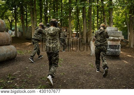 Warriors in camouflage and masks playing paintball