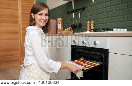 A Young Blonde Woman Takes Out Ready-made Cookies From The Oven In The Kitchen At Home. Home Confect