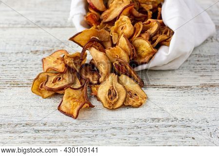 A Pile Of Dried Slices Of Pears Pills Out Of A White Pouch On Wooden Background. Dried Fruit Chips.
