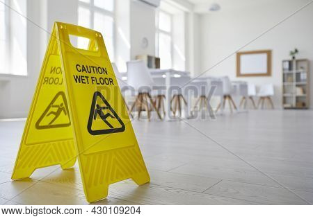 Yellow Sign With The Inscription Caution Wet Floor Which Was Put In The Office After Cleaning.