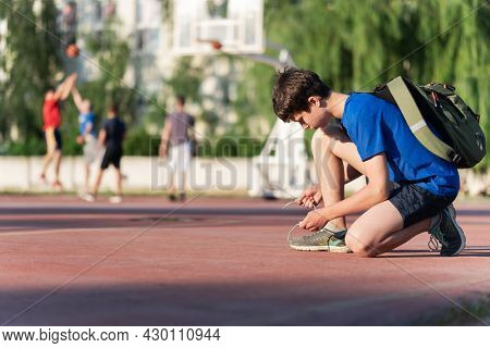 a guy ties his shoelaces on the edge of the field, next to the team playing basketball