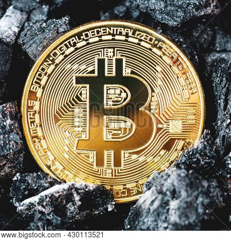 Gold Bitcoin Coin On A Black Coal Background. Gold Btc. Bitcoin Cryptocurrency